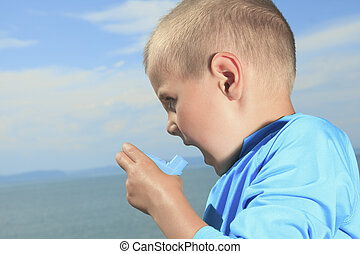A young sport boy using inhaler outside