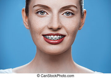 Happy beautiful girl with braces on blue background