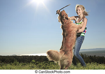 Funny girl plays with the dog outside