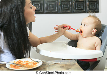Mother feeding hungry six month old baby solid food