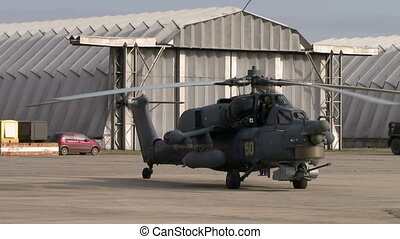 Military helicopter on background of hangars - Military...