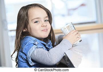 A Happy little child drinking milk on a kitchen