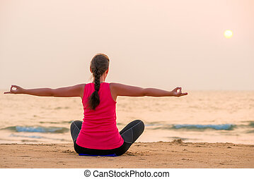 Woman in lotus position with arms outstretched to the sides