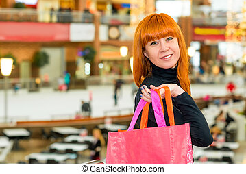 Charming red-haired girl in the mall