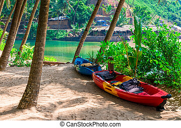 two canoes in the shade of tropical palm trees on the beach