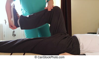 Therapist works with patient - Physical therapist working...