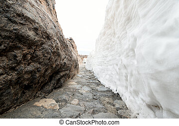 Foot path in mountains between rock wall and snow