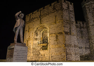 View on Lloyd George statue and Caernarfon Castle at night -...