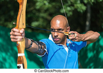 Archer aiming at target with bow and arrow - Bowman or...