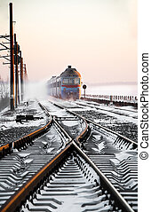 Passenger train rapidly moving along the snow track -...