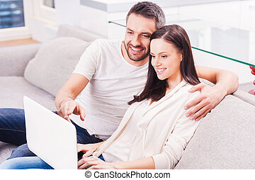 Surfing the net together. Beautiful young loving couple...