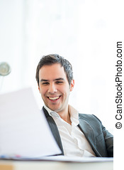 Businessman smiling as he reads a letter - Businessman...