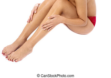 Naked woman touching her legs - Beautiful barefoot woman...