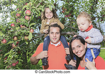 A happy family of four attractive caucasian with apple on a...