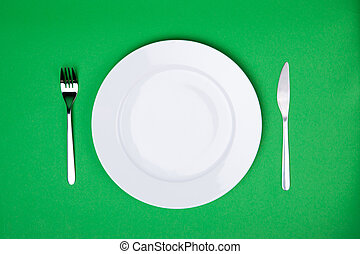 place setting with white plate, fork and knife on green background
