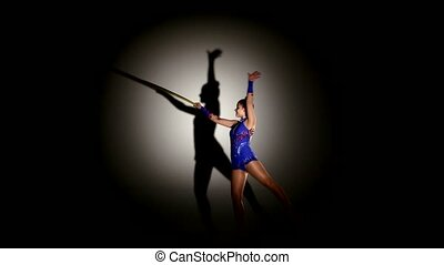 woman exercising Rhythmic Gymnastics hula hoop in silhouette...