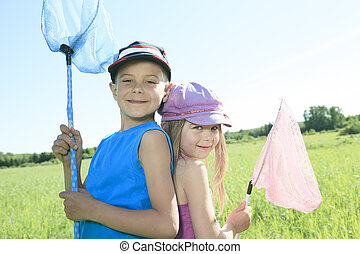 A child who try to catch some butterfly with net - A childs...