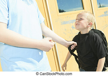 A boy bullying another in school playground