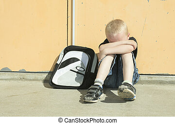 A boy bullying in school playground very sad