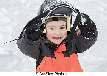 A portrait of happy child in winter play hockey