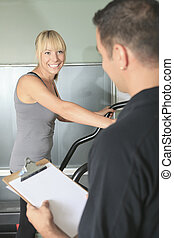 gym woman personal trainer man with weight training...