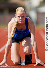Starting blocks - A teenage track athlete in the starting...