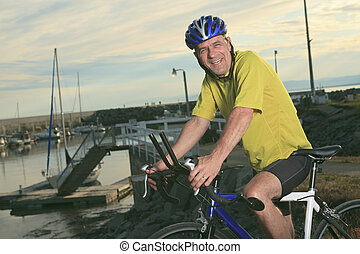 A senior man on bike at the sunset.