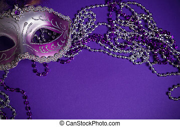 Purple Mardi-Gras or Venetian mask on purple background - A...