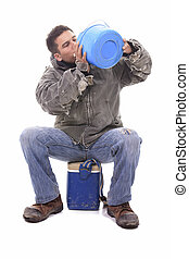 He needs a break. A young handyman holding a watering bottle