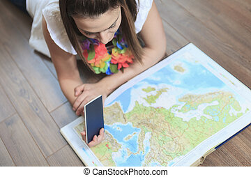 A Cheerful woman looking at a MAP in the living room