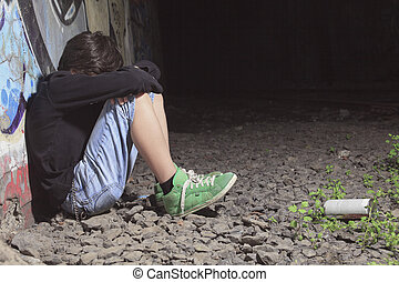 A sad teen depress at a tunnel - A teen made some graffiti...