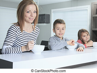 Family smiling at the camera at breakfast in kitchen