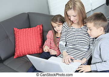 Image of friendly family sitting on the sofa and looking at...