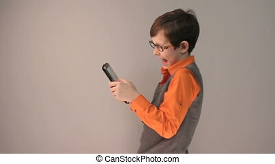 boy teenager playing tablet keen surprised in glasses on...
