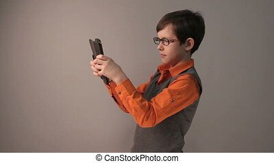 boy teenager playing tablet keen surprised in glasses gray...