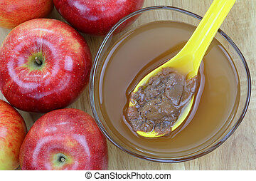 Apple cider vinegar with mother - Fresh apples and a bowl of...