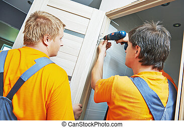 door installation workers - Two male workers carpenters at...