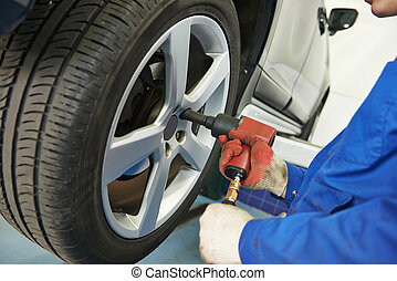 auto mechanic screwing car wheel - car mechanic screwing or...