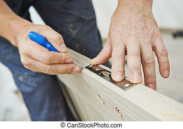 door lock installation - Close-up carpenter hands with...