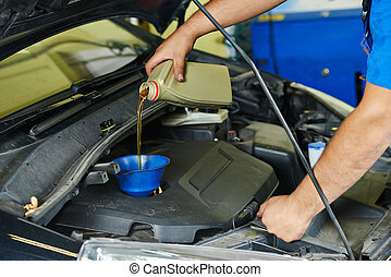 car mechanic pouring oil into motor engine - auto mechanic...