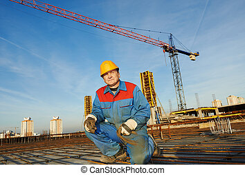 Builder making reinforcement for concrete - builder worker...