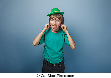 European appearance teenager boy in T-shirt with green hat stret