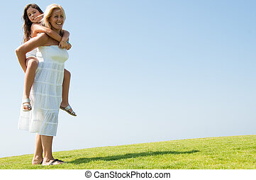 Woman giving young girl piggyback ride - Smiling young woman...