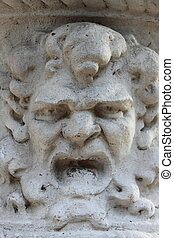 Ancient marble basrelief with an angry face