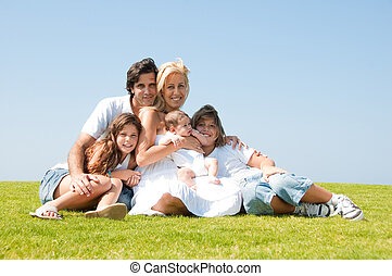 Family sitting on a grass - Happy familiy of five smiling at...