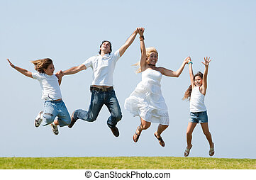 Jumping of joy - Happy family jumping high against natural...