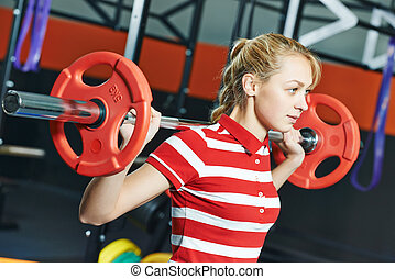 woman with weight bar in fitness gym - Young woman training...
