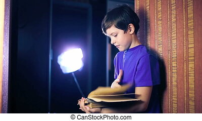 teenager boy child reads book, standing against wall in apartment page flipping