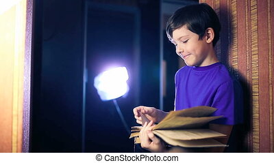 teenager boy child reads book, standing against the wall in apartment page flipping