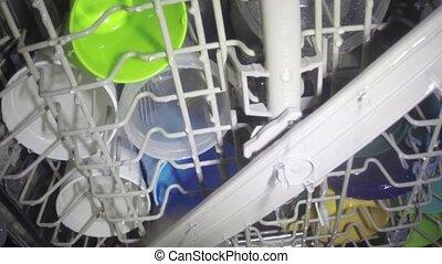 Washing dishes inside dish washer